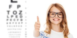 education, school, childhood, people and vision concept - smiling cute little girl with black eyeglasses showing thumbs up gesture over eye chart background